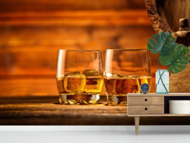 Glasses of whiskey with ice cubes served on wood