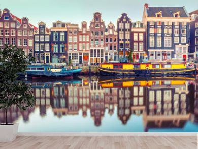 Amsterdam canal Singel with typical dutch houses and houseboats during morning blue hour, Holland, Netherlands. Used toning