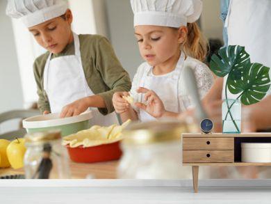 Kids in cooking class workshop preparing apple pie
