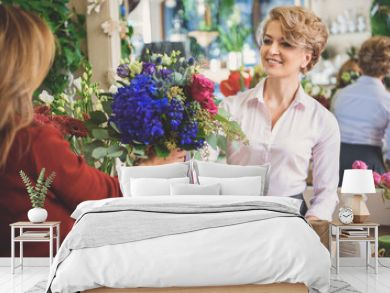 Happy woman serving customer in flower shop
