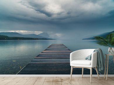 Dock overlooking a calm overcast lake.