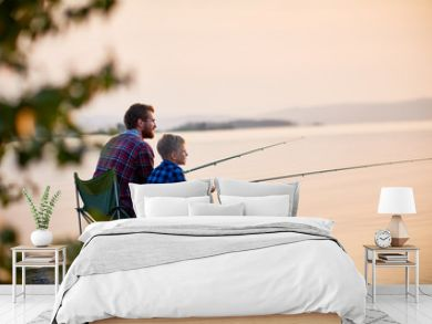 Side view portrait of father and son sitting together on rocks fishing with rods in calm lake waters with landscape of setting sun, both wearing checkered shirts, shot from behind tree
