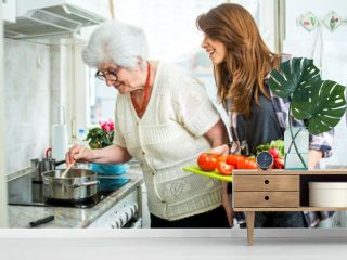 Grandmother and her granddaughter cooking together in kitchen.