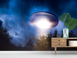 High contrast image of UFO flying over a forest with light beam at night