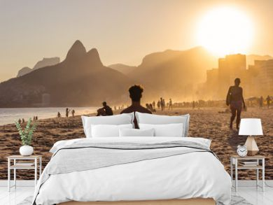 Man on yoga pose during a sunset on Ipanema beach with Morro Dois Irmãos on the background, Rio de Janeiro, Brazil