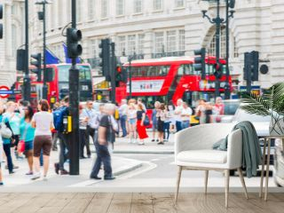 Piccadilly circus with lots of people, tourists and Londoners crossing the junction. Red bus at the background. Blurred type image