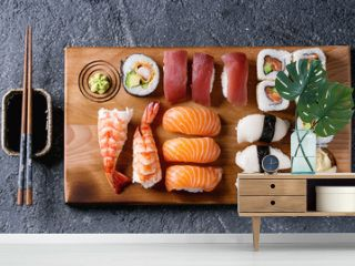 Sushi Set nigiri and sushi rolls on wooden serving board with soy sauce and chopsticks over black stone texture background. Top view with space. Japan menu