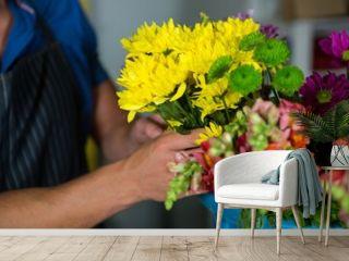 Florist holding bunch of flower in florist shop