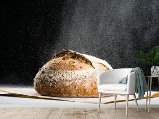 traditional round artisan rye bread loaf with walnut and seeds was sprinkled flour on wooden cutting board. Dark background