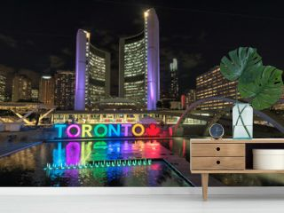 Toronto City Hall and Toronto sign in Nathan Phillips Square at night, Ontario, Canada.