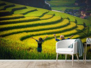 Women farmer and daughter raising armม  on Rice fields terraced at sunset in Mu Cang Chai, YenBai, Vietnam.