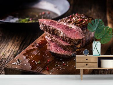 Beef steak. Juicy medium Rib Eye steak slices on wooden board with fork and knife herbs spices and salt