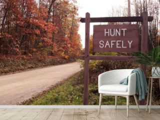 """A """"HUNT SAFELY"""" sign on the side of a dirt road in the fall woods"""