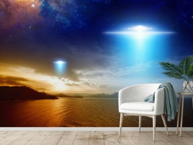 Extraterrestrial aliens spaceship fly above sunset sea