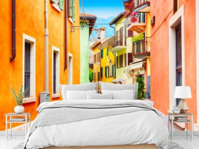 Small town narrow street view with colorful houses in Malcesine, Italy during sunny day. Beautiful lake Garda.