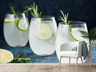 Glasses of alcoholic coctail with fresh rosemary and lime on blue background.