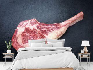 Raw dry aged wagyu tomahawk steak as close-up on black board