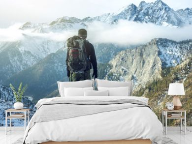 Man hiker with backpack on top of the mountain back, looking at the snow slope. Concept motivation and goal achievement