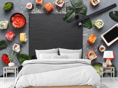 Square black slate with sushi on grey background