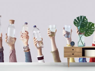 Different people holding water bottles and glass