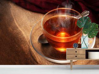 black tea freshly brewed in a glass cup, steaming hot drink on dark rustic wood, copy space