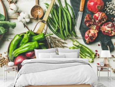 Winter vegetarian, vegan food cooking ingredients. Flat-lay of vegetables, fruit, beans, cereals, kitchen utencil, dried flowers, olive oil over white wooden background, top view. Clean eating food