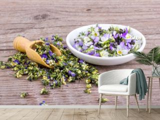 small, violet heartsease / white bowl and wooden Spoon with fresh and dried flowers from field pansy
