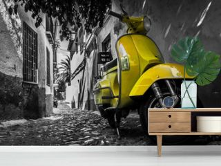 Yellow vespa scooter parked in an old empty paved street