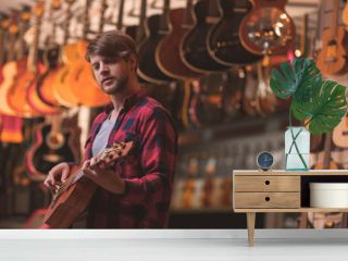 Young musician playing on a ukulele in a music store