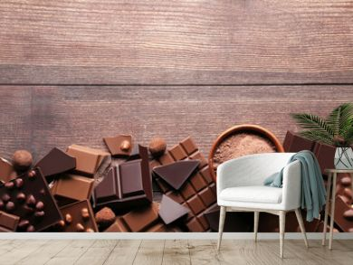Chocolate pieces with cocoa powder in bowl on wooden table