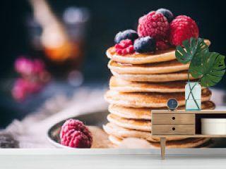 Gestapelte Pancakes mit fruschen Beeren und Ahornsirup auf dunklem Hintergrund