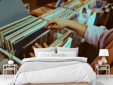 Woman is choosing a vinyl record in a musical store