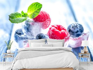 fresh berries with mint in ice cubes on wooden background