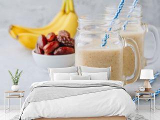 Banana and date fruit smoothie or milkshake in glass mason jar