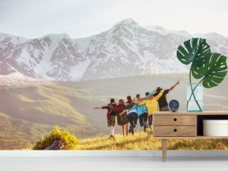Group of happy friends against mountains