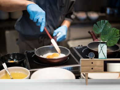 Hotel chef hands with gloves cooking fried eggs on hot pan for breakfast in restaurant at hotel.