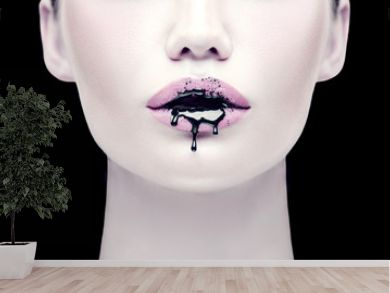 Halloween party makeup, gothic style. Black paint dripping from the lips of beautiful model girl. Beauty woman face isolated on black background