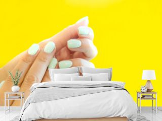 Tender hands with perfect blue manicure on trendy pastel yellow background. Place for tex