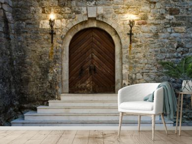 Old wooden doors of ancient castle with white staircase are illuminated by burning torches.