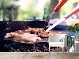 Grilling food on barbecue grill, hands preparing skewers.