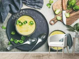 Flat-lay of seasonal brussels sprouts vegetable cream soup in black bowls and fresh green brussel sprouts on wooden board, top view. Vegan, vegetarian, healthy, dieting food concept