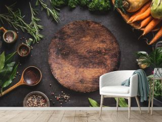Food cooking and healthy eating background with round wooden cutting board and fresh seasoning, spoon and vegetables, top view, frame. Copy space for your text and design