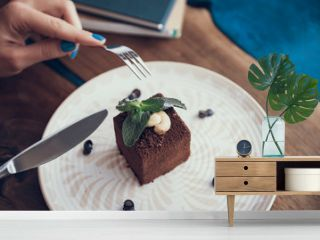 Lady with manicure holding knife and fork while getting ready for cutting delicious chocolate cake with cream berries and pepper mint