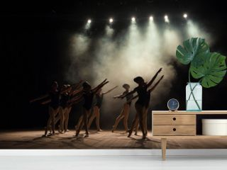 Ballet class on the stage of the theater with light and smoke. Children are engaged in classical exercise on stage.