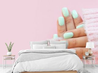Tender hands with perfect blue manicure on trendy pastel pink background. Place for tex