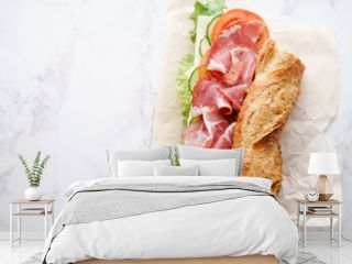 Fresh baguette sandwich bahn-mi styled. Ham, sliced cheese, tomatoes and fresh lettuce in wrapping paper on white marble background. Top view, copy space