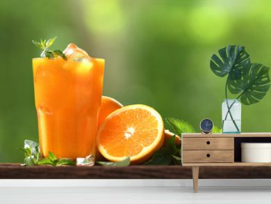 Fresh orange juice in glass with sliced orange on wood and nature background