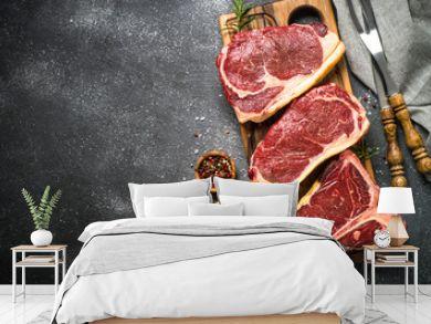 Raw meat beef steak on black top view.