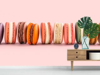 French macarons fresh large arrangement lined up on pink background