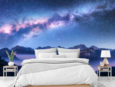 Milky Way above mountains in fog at night in autumn. Landscape with alpine mountain valley, low clouds, purple starry sky with milky way, city illumination. Aerial. Passo Giau, Dolomites, Italy. Space